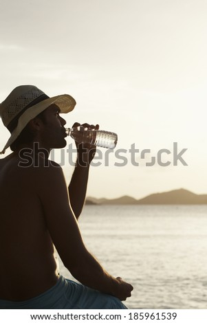Young man drinking water on beach