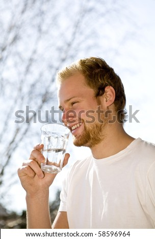 Young man drinking water  outdoors. - stock photo
