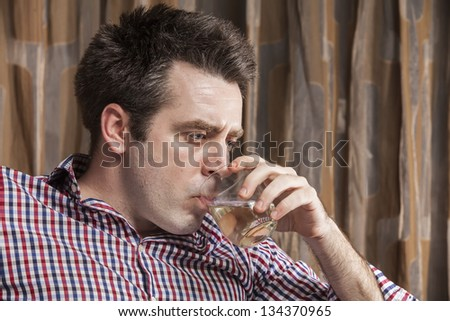 Young man drinking wine from the glass looking drunk - stock photo