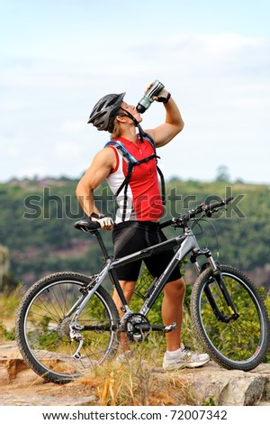 young man drinks water to quench thirst after a mountain bike cycle - stock photo