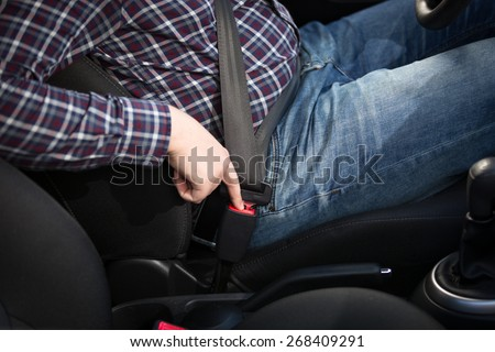 Young man driver pressing red safety belt button in car - stock photo