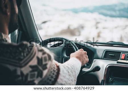 Young man drives a car in mountains. Travel and adventure concept. Selective focus. Toned picture - stock photo