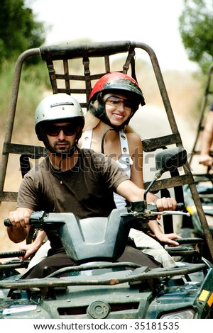 Young man drives the quad as female smiles looking towards camera - stock photo