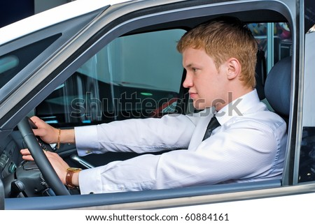 Young man driving a car in a relaxed position