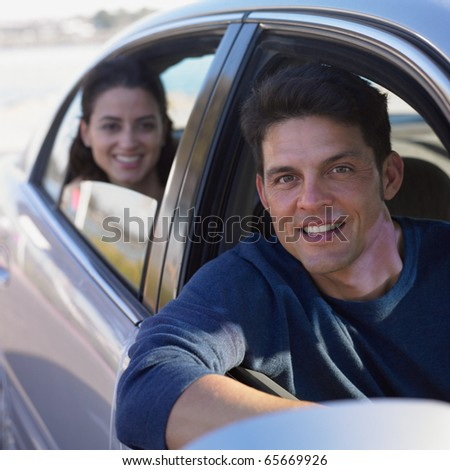 Young man driving a car with woman in backseat - stock photo