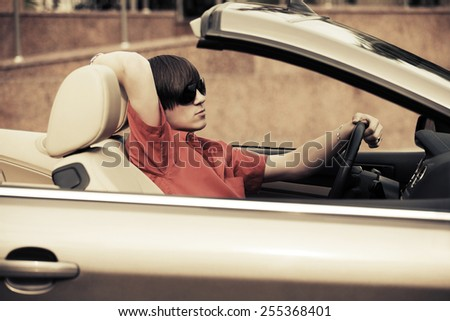 Young man driving a convertible car - stock photo