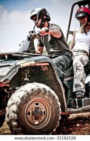 Young man driving a quad as woman enjoys it sitting at back - stock photo