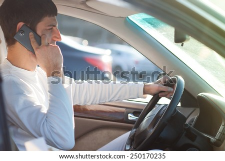 young man driving and using cell phone - stock photo