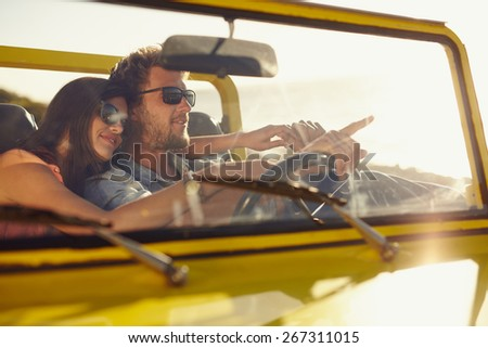 Young man driving car pointing something interesting to his girlfriend. Caucasian couple on summer holiday, Romantic couple on road trip. - stock photo