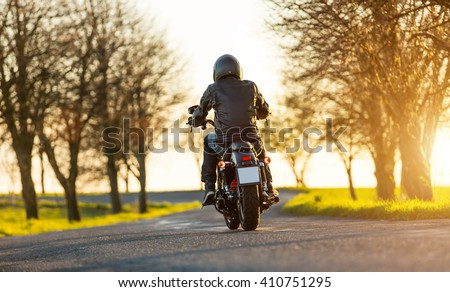 Young man driving chopper - stock photo