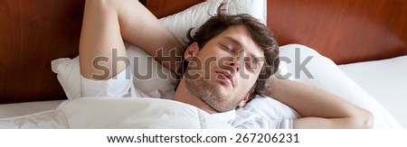 Young man during sleeping in bed, horizontal - stock photo