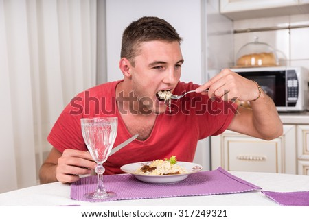 Young man eating a plate of spaghetti and meat to satisfy his hunger, with a glass of white wine in the foreground - stock photo