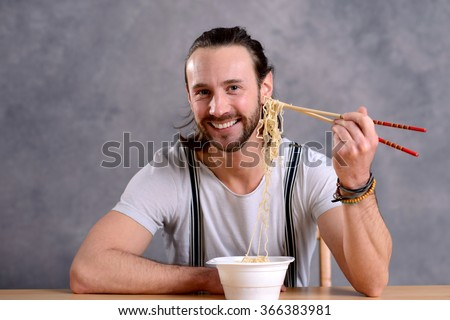 young man eating asian food and smiling in to the camera - stock photo