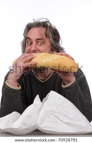 Young man eating big bread - stock photo