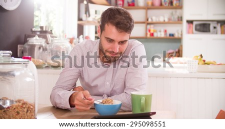 Young Man Eating Breakfast Whilst Using Digital Tablet - stock photo
