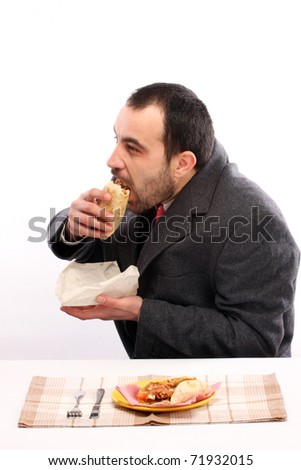 Young man eating donner kebab - stock photo