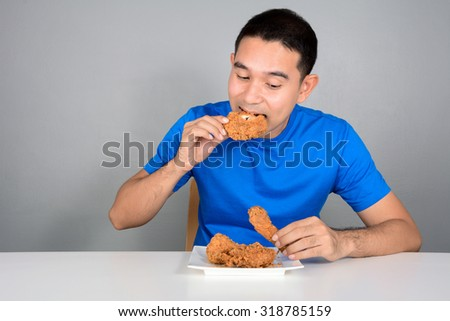 Young man eating fried chicken on the table - stock photo