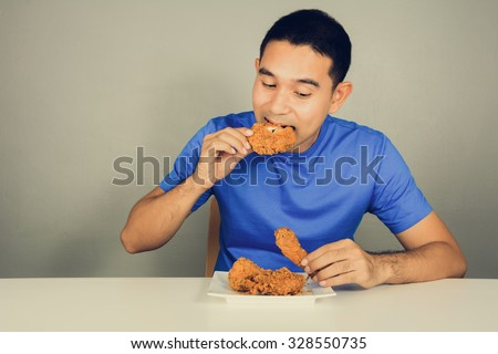 Young man eating fried chicken on the table,  vintage tone - stock photo