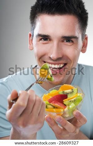 young man eating fruit close up shoot - stock photo