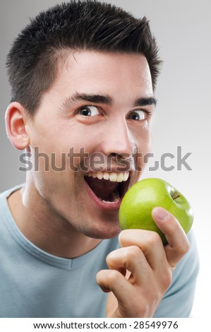 Young man eating green and healthy apple - stock photo