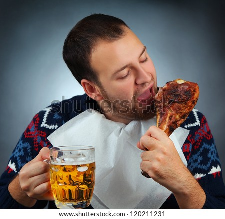 young man eating meat and drinking beer - stock photo