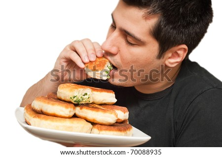 Young man eating pirojki. traditional Russian patty with eggs and onion - stock photo