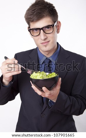 Young man eating salad and smiling. - stock photo
