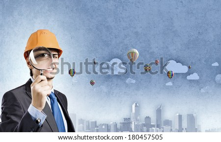 Young man engineer with magnifier against city background - stock photo