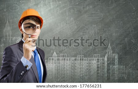 Young man engineer with magnifier against sketch background - stock photo