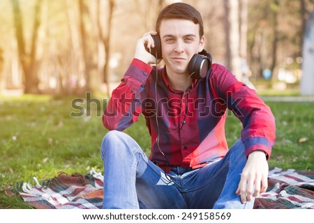 Young man enjoying and listening to the music in the park - stock photo