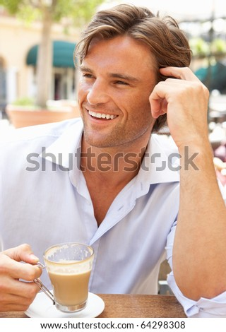 Young Man Enjoying Cup Of Coffee In Cafe
