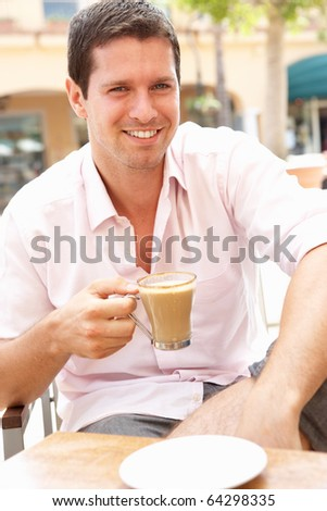 Young Man Enjoying Cup Of Coffee In Cafe - stock photo