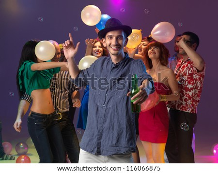 young man enjoying himself at party, holding a drink, with friends behind, playing with balloons and bubbles