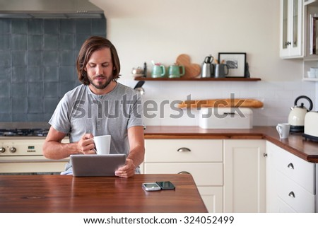 young man enjoying morning coffee with tablet computer in home kitchen - stock photo