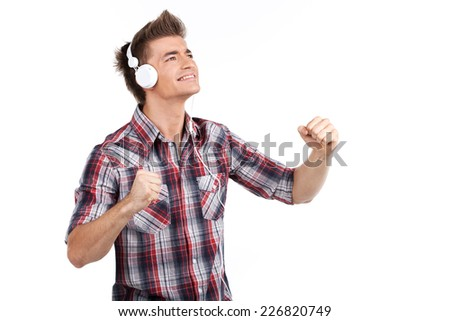 young man enjoying music on headphones. waist up portrait of boy isolated on white while listening to music - stock photo