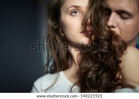 Young man enjoying smell of hair of his sweetheart - stock photo