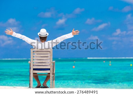 Young man enjoying summer vacation on tropical beach - stock photo
