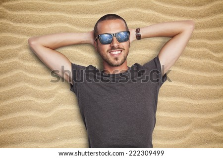 young man enjoying sun on a sandy beach looking at the sky, reflection in the sunglasses - stock photo