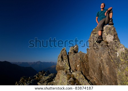 Young man enjoying sunrise in the mountains - stock photo