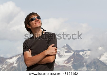 Young man enjoying the sun high in the mountains - stock photo