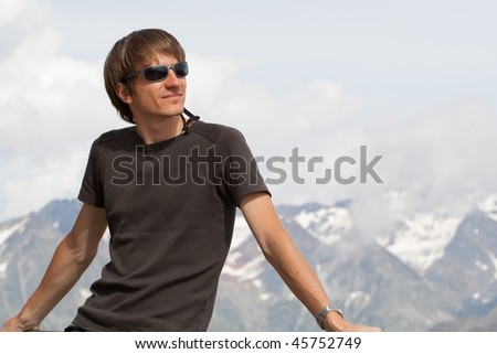 Young man enjoying the view high in the mountains - stock photo