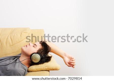 Young Man enjoys listening music in headphones - stock photo