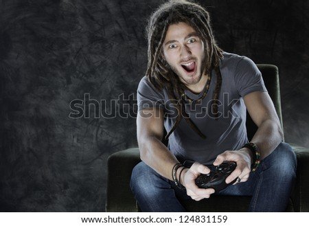 Young man enjoys playing games - stock photo
