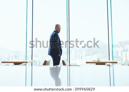 Young man entrepreneur dressed in suit is waiting for international partners in modern restaurant. Businessman is standing near skyscraper window with copy space background for advertise text message
