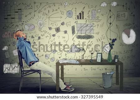 young man entrepreneur relaxing at his desk in his office - stock photo