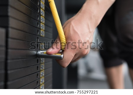 young man execute exercise with pull down machine in fitness center. male athlete select weight for training in gym. sporty asian guy working out in health club.