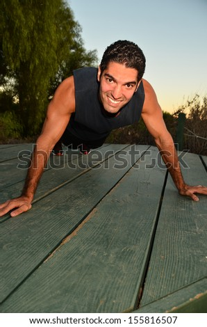 Young man exercising in outdoor environment.Physically Fir Man/Young man doing his exercises in an outdoor environment