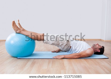 Young Man Exercising On A Pilates Ball, Indoors - stock photo