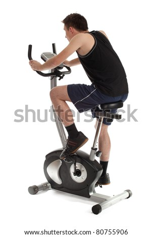 young man exercising on stationary training bicycle - stock photo