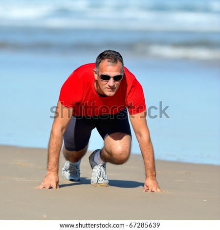 young man exercising on the beach in summer - stock photo